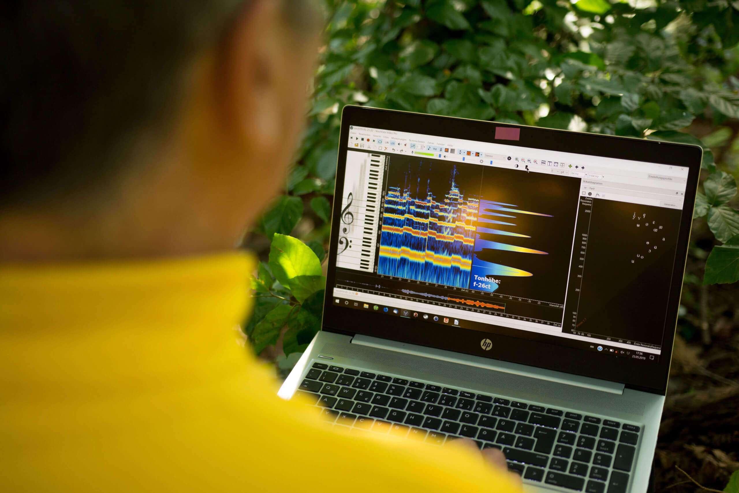 Wolfgang Saus mit Laptop und VoceVista Software in der Natur sitzend