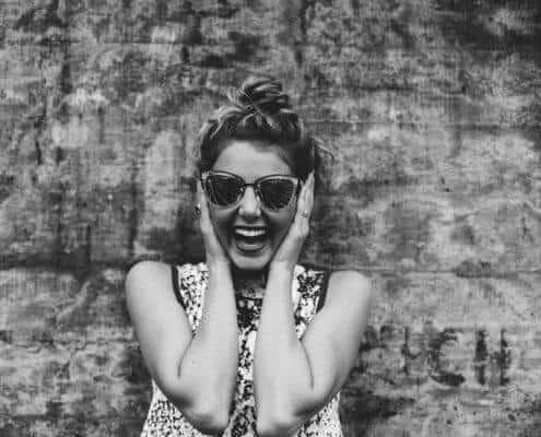 Lachende Frau hält die Ohren zu
